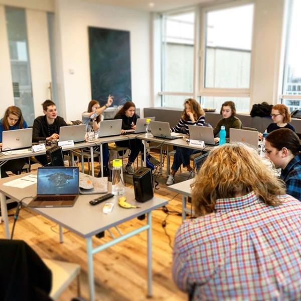 Online Workshop NEWS4U, Gruppe Jugendlicher sitzt an PCs im Kreis und erarbeitet gemeinsam etwas